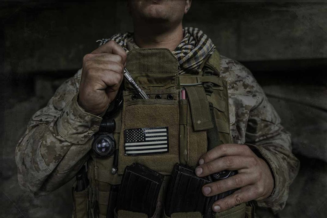 US army soldier putting tactical pen in pouch