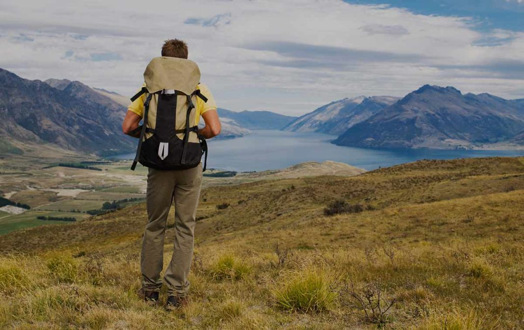 man hiking with bug out bag