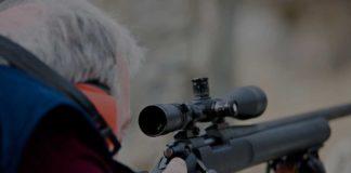 man using shotgun scope to hunt
