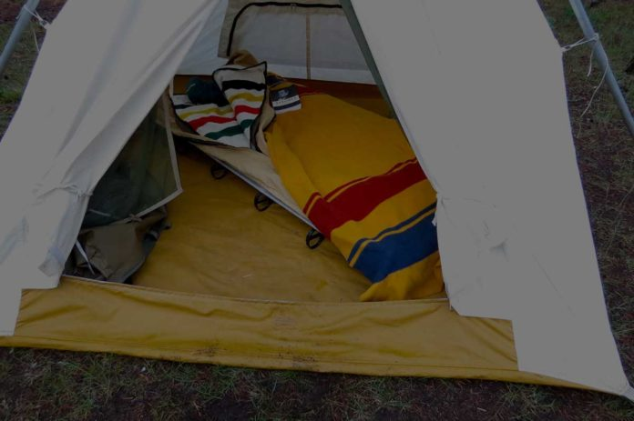 wool blanket on bed in a tent