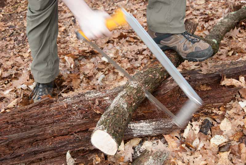 foldable camp saw being used to cut wood