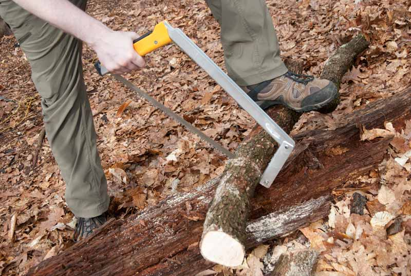 using foldable camp saw on log