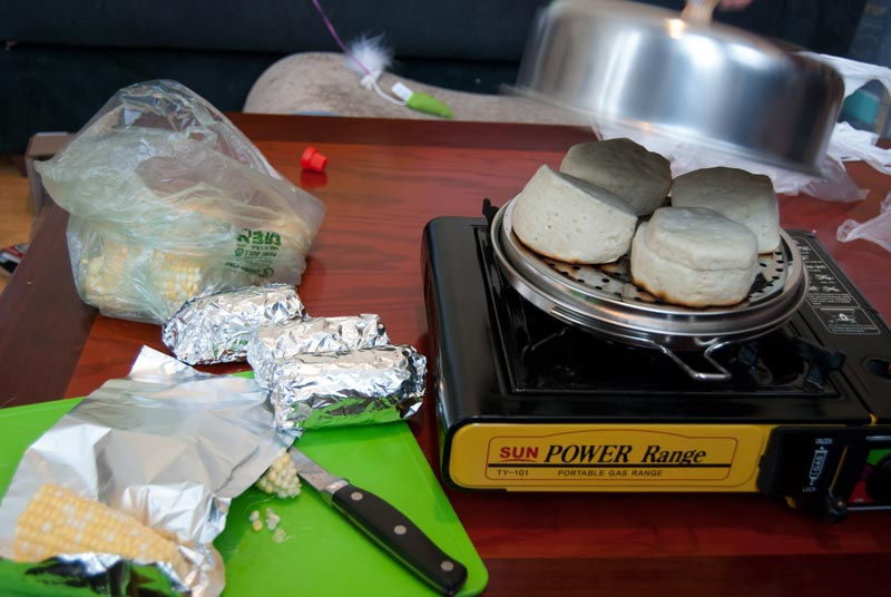 cooking corn and biscuits on potato baker