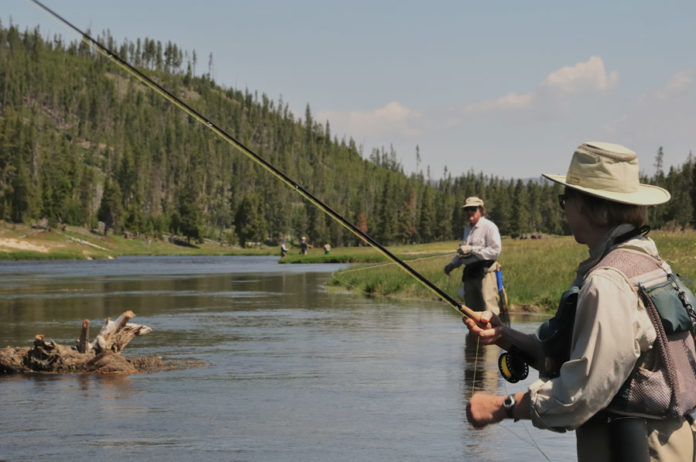 couple fly fishing in the river while wearing fishing waders