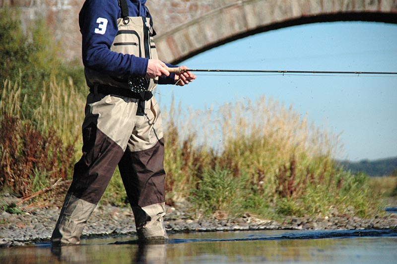 man fly fishing in river with chest waders