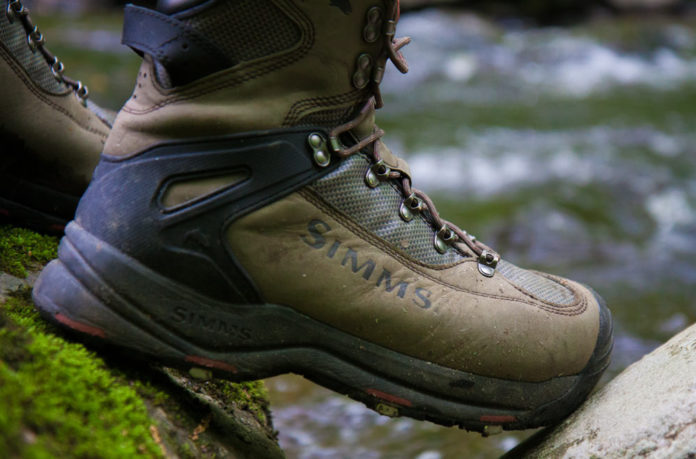 man wearing simms wading boot
