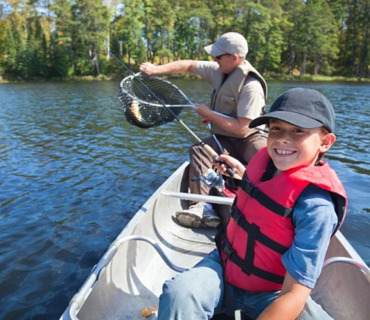 boy and father fly fishing in a canoe